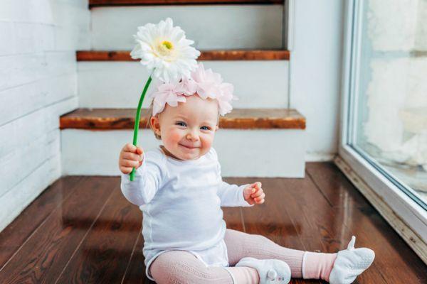 Bebé sonríe con flor