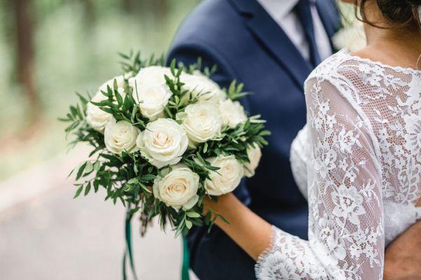 Novios abrazados y ramo de flores