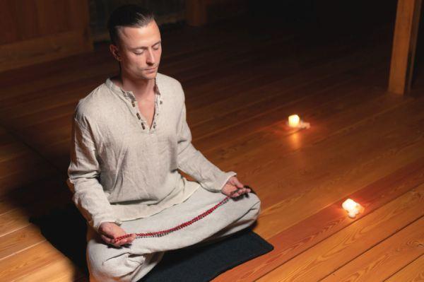 Hombre pose de loto con velas