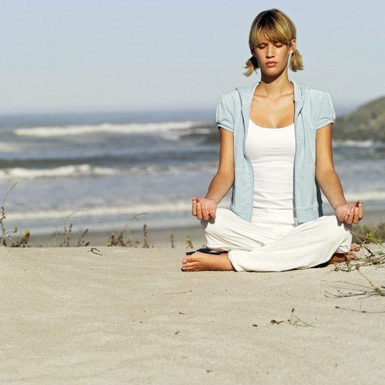 Young Woman Meditating at the Beach