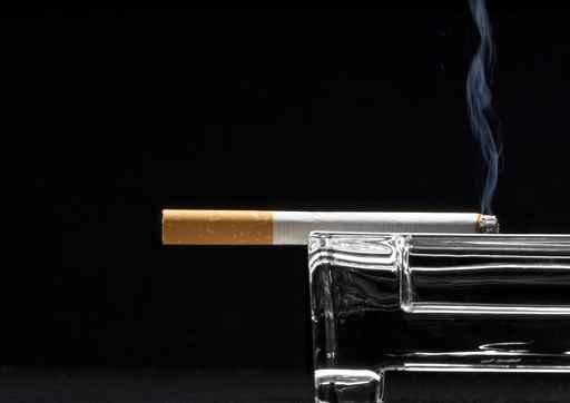 Smoldering cigarette in ashtray